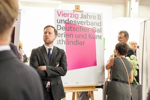 Benjamin Agert (Koelnmesse) vor dem Cover des Jubiläumsbandes